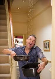 roof leaking and man catching the water